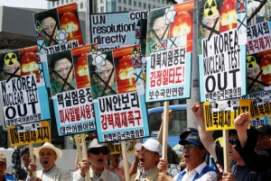South Korean protesters with defaced photos of North Korean leader Kim Jong Il shout slogans during a rally against North Korea's nuclear test near the U.S. embassy in Seoul, South Korea, Tuesday, May 26, 2009. North Korea was likely preparing to fire short range missiles off its western coast, a news report said Tuesday, a day after the country defied world powers and carried out an underground test of a nuclear bomb. (AP Photo/Ahn Young-joon)