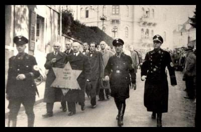 Jews_forced_to_march_with_star_Kristallnacht
