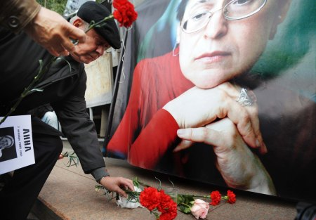 "Russian human rights activists place flowers at a portrait of slain Russian journalist Anna Politkovskaya in Moscow on October 7, 2009 during a rally on the third anniversary of her death at the hands of an unknown gunman. Three years after the killing of journalist Anna Politkovskaya, her supporters held a demonstration in her memory with the assassin and mastermind of the murder still at large. The sign reads: ""Putin we remember your cynicism."" AFP PHOTO / DMITRY KOSTYUKOV (Photo credit should read DMITRY KOSTYUKOV/AFP/Getty Images)"