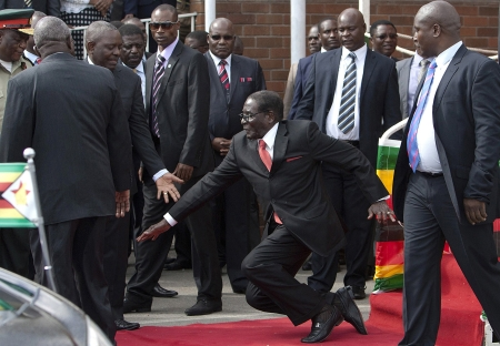 FILE - Zimbabwean President Robert Mugabe, center, falls after addressing supporters upon his return from an African Union meeting in Ethiopia, Wednesday, Feb. 4, 2015. Mugabe, 90, was elected chairman of the African Union and is set to celebrate his 91st birthday on Feb. 21. (AP Photo)